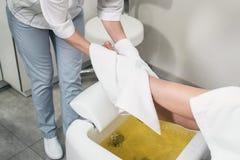 Piękne nogi dziewczyna w białym bathrobe Nowożytny piękno salon Zdjęcie Stock