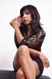 Piękne nogi krzyżujący kobiety obsiadania chwytów smartphone Obrazy Stock