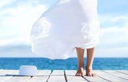 Piękne nogi młoda kobieta w bielu omijają na drewnianym molu przy latem zdjęcia stock