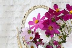 Piękne projekt wazy z kwiatami na stole z lustrem wewnątrz Obraz Royalty Free