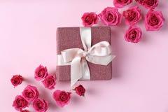 Piękne róże i prezenta pudełko na koloru tle fotografia stock
