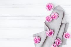 Piękne różowe róże na szarym bieliźnianym tkaniny tablecloth Dekoracyjna rama na białego rocznika drewnianym stole Mieszkanie nie fotografia royalty free