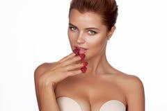 Piękne seksowne brunetki kobiety łasowania malinki na białym tle, zdrowy jedzenie, smakowity jedzenie, organicznie Fotografia Stock