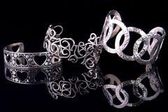 Piękne srebne bransoletki na czarnym tle Zdjęcia Royalty Free