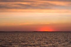 Piękne szkarłatne zmierzchu i spokoju fala na jeziorze Fotografia Stock