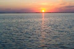 Piękne szkarłatne zmierzchu i spokoju fala na jeziorze Zdjęcia Stock