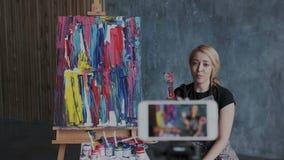 Pięknego blondynka żeńskiego artysty magnetofonowy wideo blog o współczesnej technice obraz Ona opowiada zwolennicy