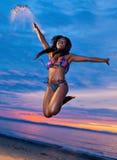 Pięknego czarnego afrykanina kobiety Amerykański doskakiwanie na plaży przy s Fotografia Stock