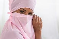 Pięknego czarnego afrykanina muzułmańska kobieta jest ubranym różowego chustka na głowę Zdjęcia Royalty Free