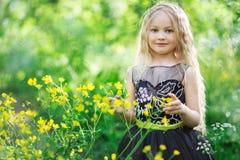 Pięknego dziecka dziewczyna w koloru żółtego ogródzie Zdjęcia Royalty Free