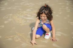 Pięknego dziecka writing na plażowym piasku zdjęcie royalty free