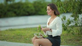 Pięknego kobiety łasowania sałatkowy obsiadanie w pić smoothie i parku zbiory wideo