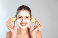 Pięknego kobiety mienia ogórkowi plasterki blisko jej twarzy z gliny maską przeciw popielatemu tłu zdjęcie royalty free