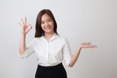 Pięknego młodego Azjatyckiego kobiety przedstawienia palmowa ręka i OK podpisujemy Zdjęcie Stock