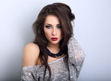 Pięknego młodego ekspresyjnego makijażu wzorcowy pozować w popielatej bluzce w fotografia stock