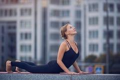 Pięknego młodych kobiet praktyk joga asana obszycia oddolny pies Urdhva Mukha Svanasana outdoors przeciw tłu nowożytny ci zdjęcie stock
