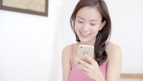 Pięknego portret kobiety młodego azjatykciego uśmiechniętego trwanie przyglądającego mądrze telefonu komórkowego czytelnicza ogól zdjęcie wideo