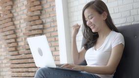 Pięknego portreta azjatykcia młoda kobieta pracuje online laptop z uśmiechem i szczęśliwym obsiadaniem na leżance przy żywym poko zbiory