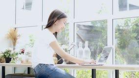 Pięknego portreta azjatykcia młoda kobieta pracuje online laptop z uśmiechem i szczęśliwym obsiadaniem przy kawiarnia sklepem zdjęcie wideo