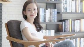 Pięknego portreta kobiety młody azjatykci obsiadanie na kanapie z uśmiechem, szczęśliwy przy żywym pokojem i zbiory wideo