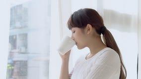 Pięknego portreta kobiety młody azjatykci uśmiech i pije filiżanka kawy z relaksuje zbiory