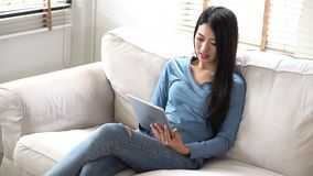Pięknego portreta kobiety młody azjatykci uśmiech i szczęśliwy używa cyfrowej pastylki komputerowy obsiadanie na leżance przy żyw zbiory