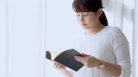 Pięknego portreta młoda azjatykcia kobieta i czasu wolnego trwanie uczenie z czytelniczą książką dla egzaminu w sypialni relaksuj zbiory