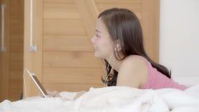 Pięknego portreta młoda azjatykcia kobieta kłama szczęśliwej słuchawki słuchającą muzykę z relaksuje i cieszy się w sypialni zbiory wideo