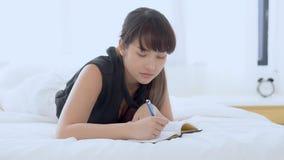 Pięknego portreta młoda azjatykcia kobieta relaksuje lying on the beach na łóżkowym myślącym pomysle i pisać dzienniczek lub ksią zbiory wideo