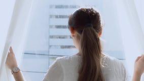 Pięknego portreta młoda azjatykcia kobieta relaksuje otwarte zasłony przy nadokienny patrzeć outside z nadzieją i przyszłością w  zbiory