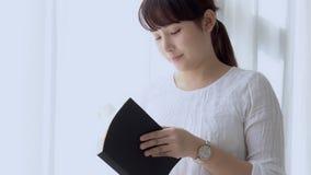 Pięknego portreta młoda azjatykcia kobieta relaksuje trwanie uczenie z czytelniczą książką dla egzaminu w sypialni w domu zdjęcie wideo