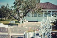 Pięknego rocznika ślubna ceremonia outdoors Lato Stary biały drewniany dom Drzewo dekorował z białymi klatkami kwiaty pełno zdjęcia stock
