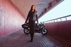Pięknego rowerzysta dziewczyny mienia hełma następny superbike chodzi na chodniczku wśrodku mostu obraz stock