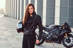 Pięknego rowerzysta dziewczyny mienia hełma następny superbike na zewnątrz budynku fotografia stock