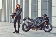 Pięknego rowerzysta dziewczyny mienia hełma następny superbike na zewnątrz budynku obraz royalty free