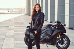 Pięknego rowerzysta dziewczyny mienia hełma następny superbike na zewnątrz budynku obrazy royalty free