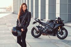 Pięknego rowerzysta dziewczyny mienia hełma następny superbike na zewnątrz budynku zdjęcie royalty free