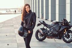 Pięknego rowerzysta dziewczyny mienia hełma następny superbike na zewnątrz budynku obraz stock