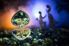 Pięknego rozpieczętowanego starego rocznika srebra sercowata szkatuła z obrączkami ślubnymi z sylwetką zostaje na ma i kolanie mł Fotografia Stock