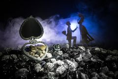 Pięknego rozpieczętowanego starego rocznika srebra sercowata szkatuła z obrączkami ślubnymi z sylwetką zostaje na ma i kolanie mł Obraz Stock