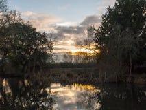 Pięknego słońca jesieni światła ustalony niebo nad rzecznymi drzew odbiciami Obrazy Stock