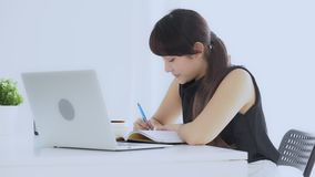 Pięknej azjatykciej kobiety uśmiechnięty obsiadanie w nauce pisze notatniku w domu żywym izbowym uczenie i zdjęcie wideo