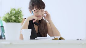 Pięknej azjatykciej kobiety uśmiechnięty obsiadanie w nauce pisze notatniku w domu żywym izbowym uczenie i zbiory
