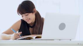 Pięknej azjatykciej kobiety uśmiechnięty obsiadanie w nauce pisze notatniku w domu żywym izbowym uczenie i zbiory wideo