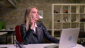 Pięknej blondynki caucasian bizneswoman wiesza na telefonie z spokój koncentrującą twarzą podczas gdy siedzący przy desktop pobli