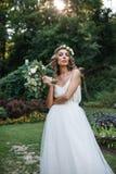 Pięknej blondynki szczęśliwa panna młoda w eleganckiej biel sukni w wianku z bukietem outdoors zdjęcia royalty free