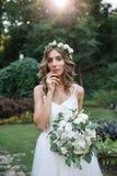 Pięknej blondynki szczęśliwa panna młoda w eleganckiej biel sukni w wianku z bukietem outdoors zdjęcia stock
