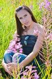Pięknej brunetki żeński obsiadanie w polu zdjęcia royalty free