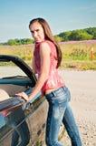 Pięknej brunetki żeński trwanie pobliski samochód zdjęcia stock