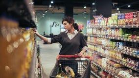 Pięknej brunetki dziewczyny chodząca synklina nawa w sklepie spożywczym próbuje wybierać jaki sause kupować Zrywania szkło zdjęcie wideo